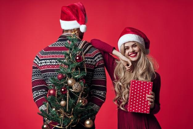 Casal jovem alegre feriado decoração de presente de natal com fundo vermelho