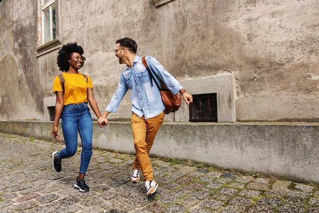 Casal jovem alegre hippie multicultural andando em uma parte antiga da cidade e de mãos dadas.