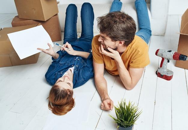 Casal jovem alegre na sala no sofá com caixas
