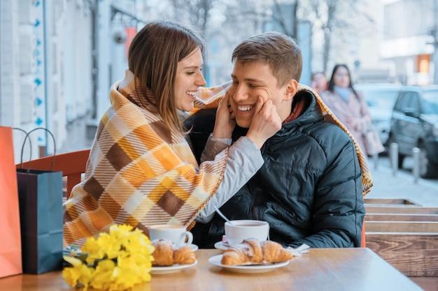 Casal jovem alegre no café ao ar livre, rindo e se divertindo sob xadrez