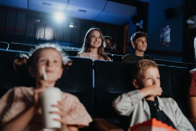 Casal jovem alegre no cinema, assistindo filme.