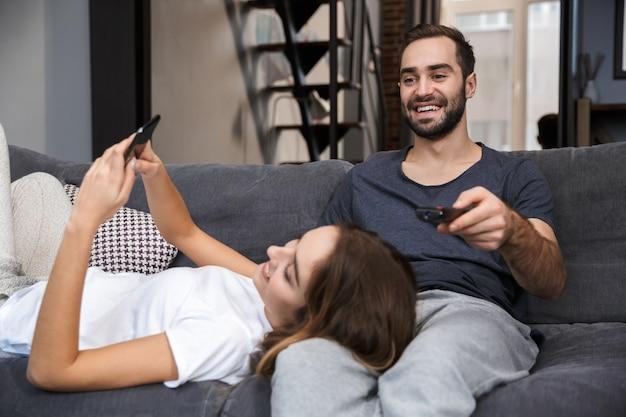 Casal jovem alegre relaxando no sofá em casa, assistindo tv