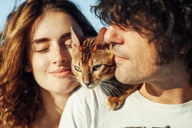Casal jovem alegre se divertindo na praia com seu gato de bengala