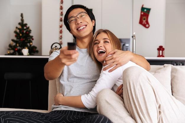 Casal jovem alegre, sentado em um sofá em casa, se abraçando, homem segurando o controle remoto da tv