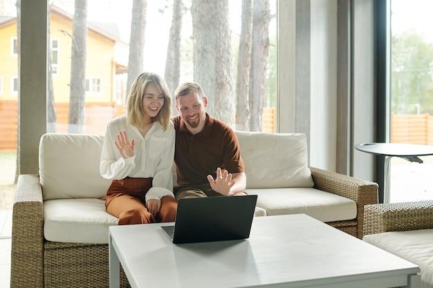 Casal jovem alegre sentado no sofá e acenando com as mãos para o laptop enquanto conversa via link de vídeo na sala de estar de uma casa de campo