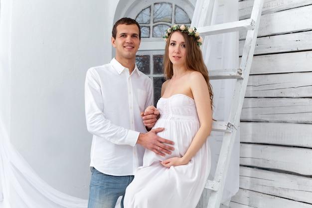 Casal jovem alegre, vestido de branco em pé em casa