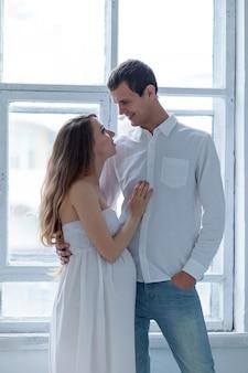 Casal jovem alegre, vestido de branco, sentado no sofá