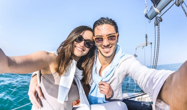 Casal jovem amante tendo selfie no passeio de barco à vela ao redor do mundo