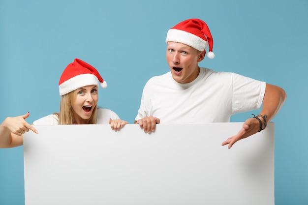 Casal jovem amigo do papai noel espantado, cara e mulher com chapéu de natal