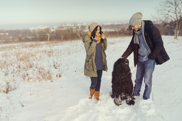 Casal jovem andando com um cachorro em um dia de inverno