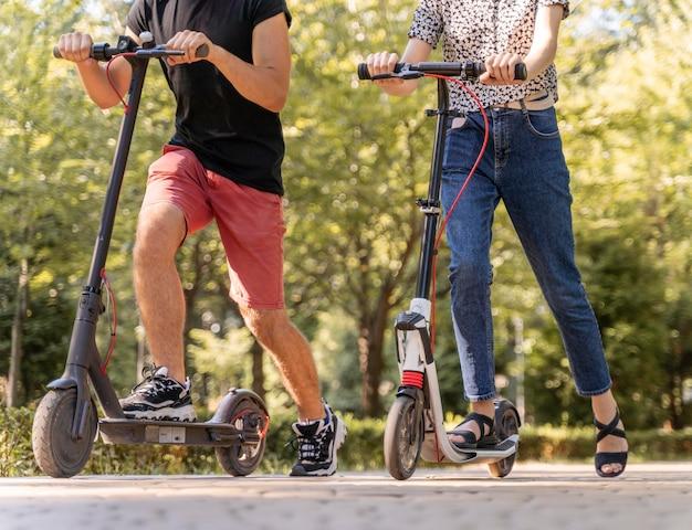 Casal jovem andando de scooters ao ar livre