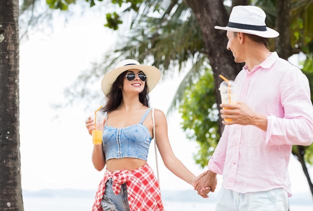 Casal jovem andando no parque na beira-mar de mãos dadas