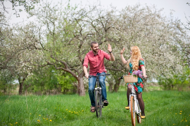 Casal jovem apaixonado, andar de bicicleta no jardim primavera