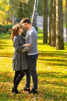 Casal jovem apaixonado e moderno em um parque de outono em um abraço apertado, olhando nos olhos um do outro com amor