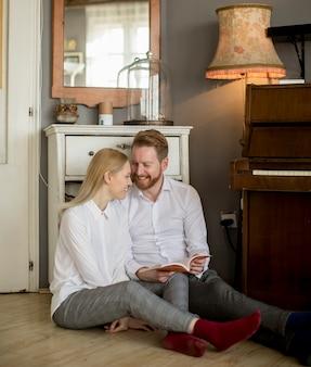 Casal jovem apaixonado, lendo um livro no quarto