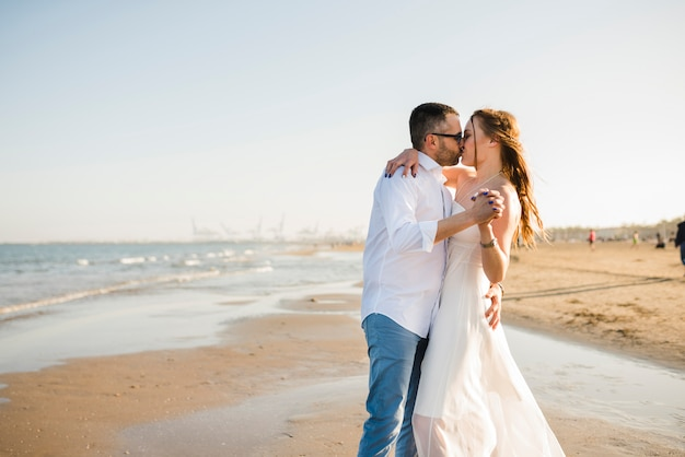 Casal jovem apaixonado, segurando a mão do outro, beijando uns aos outros na praia de verão