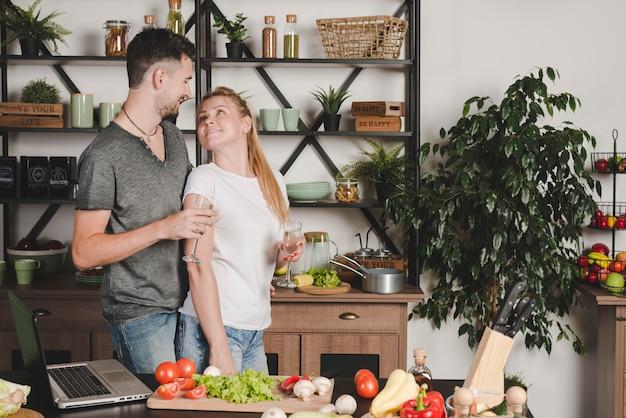 Casal jovem apaixonado segurando a taça de champanhe em pé na cozinha