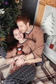 Casal jovem apaixonado, sentado no chão perto da árvore de natal na manhã de natal, acariciando. família feliz
