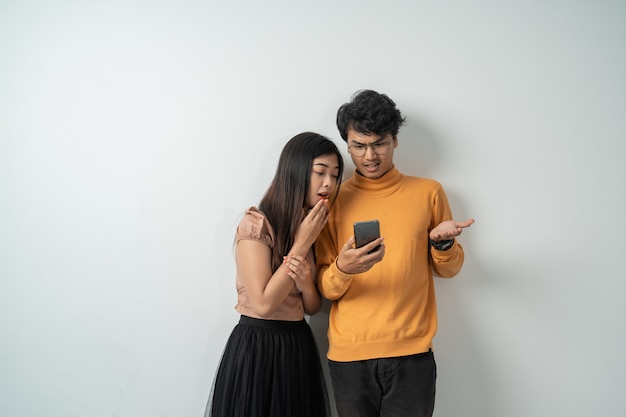 Casal jovem asiático em pé olhando para a tela de um telefone inteligente expressão de surpresa