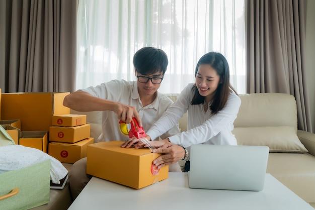 Casal jovem asiático está vendendo on-line através de um computador e ajudando a embalar o pedido do cliente em caixas