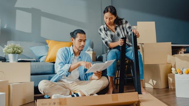 Casal jovem asiático feliz e atraente, homem e mulher se ajudam a desempacotar a caixa e montar os móveis