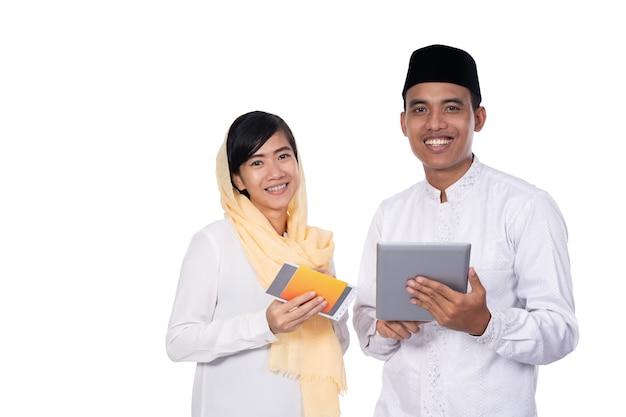 Casal jovem asiático muçulmano usando o tablet pc