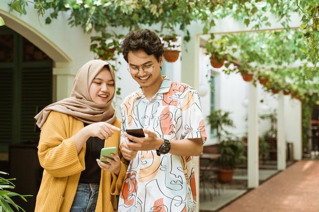 Casal jovem asiático riu enquanto segura um telefone celular