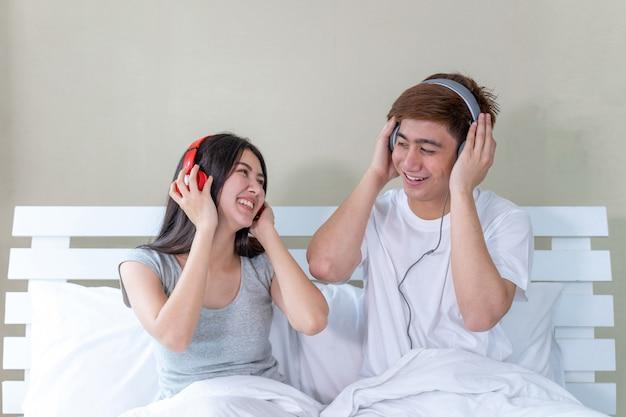 Casal jovem asiático sentado na cama e usando fones de ouvido para ouvir música e dançar alegremente