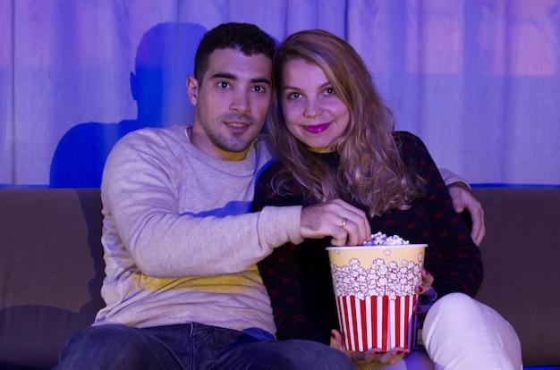 Casal jovem assistindo filme de suspense em um quarto escuro com pipoca no sofá.