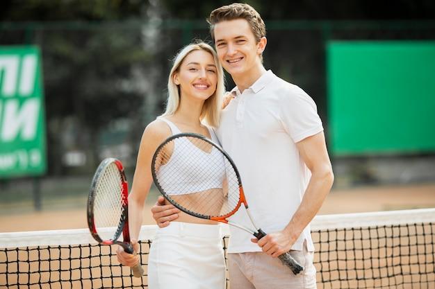 Casal jovem ativo com raquetes de tênis