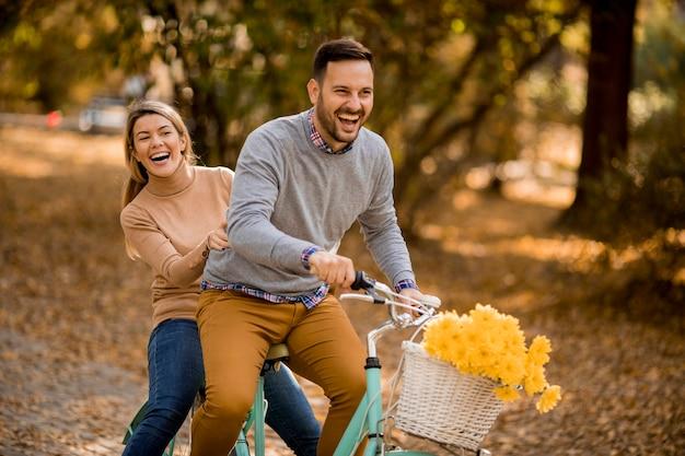 Casal jovem ativo desfrutando juntos em andar de bicicleta no parque outono dourado