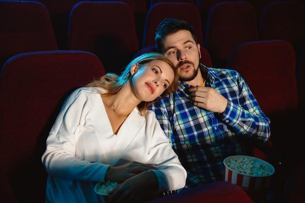 Casal jovem atraente assistindo a um filme no cinema