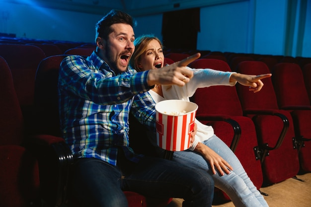 Casal jovem atraente caucasiano assistindo a um filme no cinema, casa ou cinema. pareça expressivo, surpreso e emocionado. sentado sozinho e se divertindo. relação, amor, família, tempo de fim de semana.