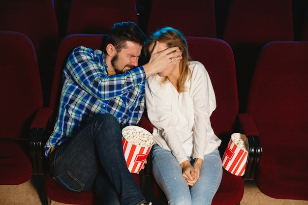 Casal jovem atraente caucasiano assistindo a um filme no cinema, casa ou cinema.