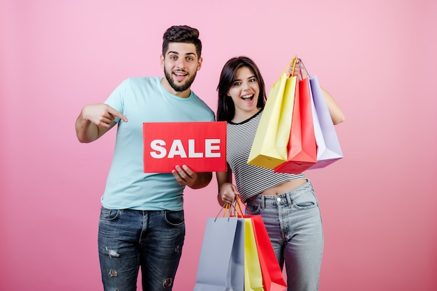 Casal jovem atraente homem e mulher com sinal de venda e sacolas coloridas