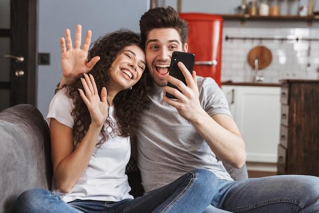 Casal jovem atraente homem e mulher sentados no sofá em casa tirando uma foto de selfie juntos no smartphone