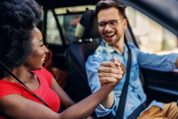 Casal jovem atraente multicultural hippie sentado no carro e de mãos dadas.