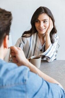 Casal jovem atraente tomando café pela manhã em casa, sentado à mesa