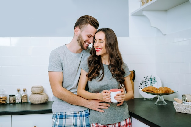Casal jovem atraente vestido com roupa casual comemorando o dia de são valentim juntos em casa compartilhando presentes em uma cozinha aconchegante