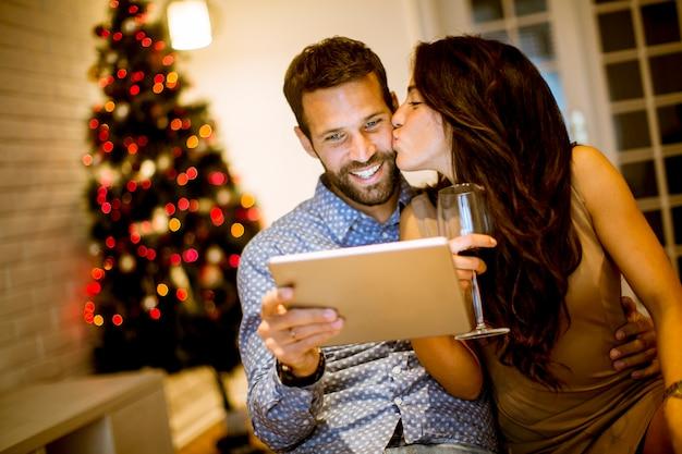 Casal jovem bonito com tablet na véspera de ano novo
