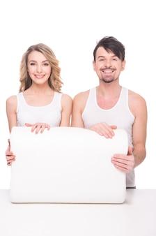 Casal jovem bonito com travesseiro macio de qualidade.