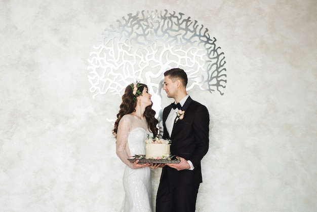 Casal jovem bonito em pé e segurando um bolo de casamento com casamento interior luxuoso