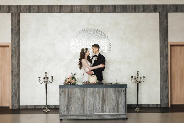 Casal jovem bonito em pé e segurando um bolo de casamento com interior luxuoso