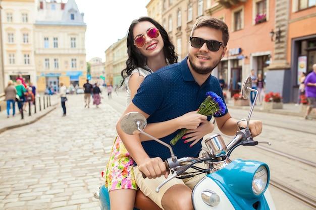 Casal jovem bonito hippie andando na rua de motocicleta