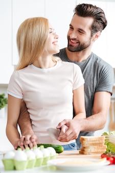 Casal jovem bonito juntos a preparar salada saudável