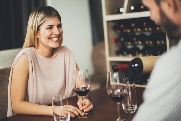 Casal jovem bonito na data sentado por tabela em bar de vinhos