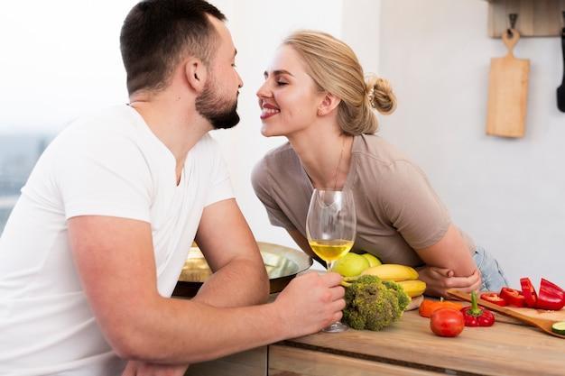Casal jovem bonito sentados juntos na cozinha