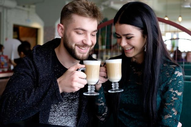 Casal jovem branco bebendo cappuccino no café e sorrindo