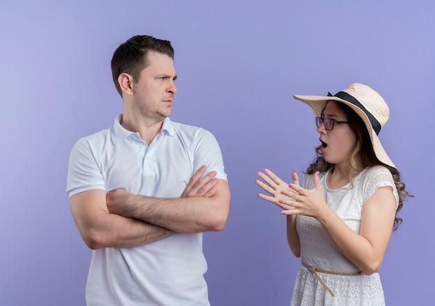 Casal jovem brigando com mulher frustrada olhando com raiva para o namorado enquanto ele carranca em pé sobre a parede azul