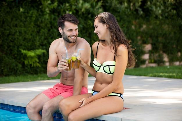 Casal jovem brindando chá gelado à beira da piscina em um dia ensolarado